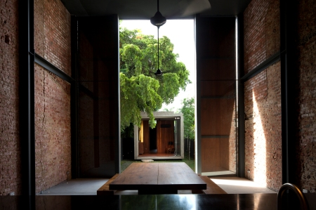 50f861f9b3fc4b316d000253_lucky-shophouse-chang-architects_when_the_sliding_door_panels_open_-_a_framed_view_of_the_rear_house_from_the_kitchen_dining_a